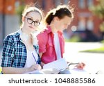 young happy students with books ... | Shutterstock . vector #1048885586