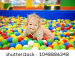 curly little girl having fun in ... | Shutterstock . vector #1048886348