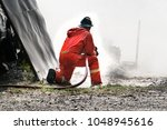 fire man spray water to... | Shutterstock . vector #1048945616