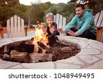 view of firepit and happy... | Shutterstock . vector #1048949495