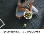 young woman eating salad... | Shutterstock . vector #1049020955