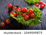 salad and tomatoes on a black... | Shutterstock . vector #1049049875