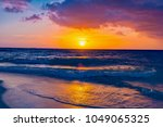 Brilliant vacation destination beach sunrise with colorful sand bright sea foam pink clouds  - stock photo