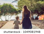 mother and son go to the sea... | Shutterstock . vector #1049081948
