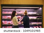 women purchasing a packet of... | Shutterstock . vector #1049101985