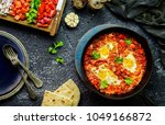 Small photo of Middle Eastern traditional food; Shakshuka skillet served with pita bread and placed with fresh chopped vegetables. Top view with close-up