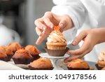 woman decorating tasty cupcake... | Shutterstock . vector #1049178566