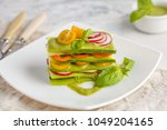 Stock photo raw zucchini lasagna with vegetables and pesto sauce light background vegetarian raw diet concept 1049204165