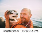 dog and owner on yacht bord on...   Shutterstock . vector #1049215895