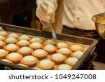 the baker's hand holding bakery ... | Shutterstock . vector #1049247008