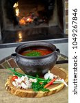 Small photo of Ukrainian borsch on the fire with greens and bacon