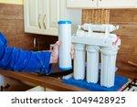 installing a water filter | Shutterstock . vector #1049428925