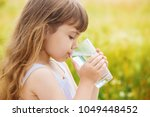 the child holds a glass of... | Shutterstock . vector #1049448452