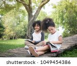 two adorable kids reading a... | Shutterstock . vector #1049454386