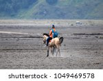 ride a horse on the volcano... | Shutterstock . vector #1049469578