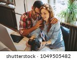 young couple looking photos on... | Shutterstock . vector #1049505482