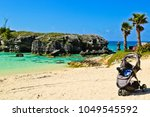 a baby trolley on the beach of... | Shutterstock . vector #1049545592