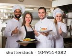 waitress and cooking team at... | Shutterstock . vector #1049554382