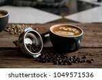 hot latte coffee in black cup... | Shutterstock . vector #1049571536