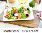fresh greek salad on a plate on ...   Shutterstock . vector #1049576525