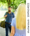 Small photo of Casual encounter, acquaintance, start of relations. First meet of strangers, man with beard looks at blonde girl. Love at first sight concept. Meet on sunny summer day, nature background, defocused.