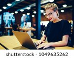 Small photo of Young gorgeous smiling internet user in cool spectacles keyboarding email message for customer via laptop connected to wireless. Charming cheerful hipster girl sending messages to friends online