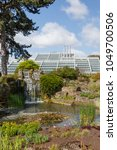 Small photo of London, UK - April 18, 2014. Rock garden and Princess of Wales Conservatory in Kew Botanic Gardens. The gardens were founded in 1840 and are of international significance for botanical research.