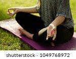 women meditating in grass on...   Shutterstock . vector #1049768972