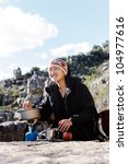 Portrait of an asian chinese backpacker cooking on a camping gas stove while hiking and exploring on a tourist adventure in the wilderness mountains - stock photo