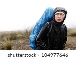portrait of asian hiker with waterproof gear and backpack in the rain while trekking on an adventure expedition in the mountains during bad weather, cold and miserable - stock photo