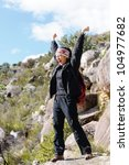 Happy celebrating hiker with arms up after reaching the summit of a wilderness trak - stock photo
