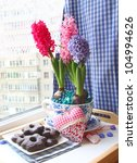 Hyacinths in a beautiful pot with a chocolate thin captain on a window - stock photo