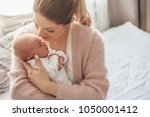 home portrait of a newborn baby ... | Shutterstock . vector #1050001412