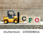 Small photo of Toy yellow forklift hold letter block C to complete word CFO (Abbreviation of Chief Financial Officer) on wood background