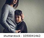 Sad Little Boy Being Hugged By...