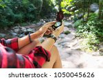hiking woman holding a compass. ... | Shutterstock . vector #1050045626
