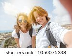 two attractive young girls... | Shutterstock . vector #1050075338