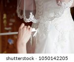 the bride is helped by the maid ... | Shutterstock . vector #1050142205