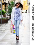 Portrait of a beautiful young woman with shopping bags in shopping street - stock photo