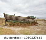 wrecked wooden fisher boat.... | Shutterstock . vector #1050227666