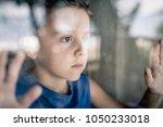 one sad little boy standing... | Shutterstock . vector #1050233018