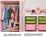 a little girl is sitting in a... | Shutterstock . vector #1050245495