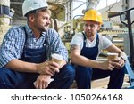 portrait of two workers wearing ... | Shutterstock . vector #1050266168