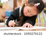 little girl drawing a picture | Shutterstock . vector #1050270122
