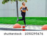 a beautiful sporty woman runing ... | Shutterstock . vector #1050295676
