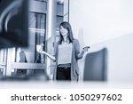 female speaker giving... | Shutterstock . vector #1050297602