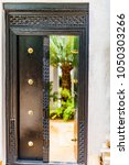 Small photo of Traditional Swahili carved mahogany entrance door, with brass studs. One side open, tempting the onlooker to peer inside. Bokeh internal garden with lush green palm fronds. Shela, Lamu, Kenya, Africa