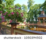 Small photo of Saint Petersburg, Russia - August 9, 2017: Vase with flowers next to Menagerie Pond Bosquet in The Summer Garden in St. Petersburg. The park was personally designed by Czar Peter in 1704