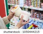 buyer hands with plastic yogurt ... | Shutterstock . vector #1050444215