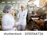 Small photo of Focused dedicated tired female employee giving rapport in food production factory to her worried and annoyed superior while holding statistic notes and wearing sterile cloths.